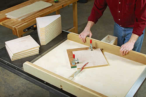 Angle-cutting the 16 braces to shape is quick and safe with a crosscut sled. Here the author secures each blank for cutting with a pair of toggle clamps mounted on fences that are attached to the sled's bed.