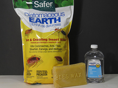 Bag of diatomaceous earth, bar of beeswax and bottle of mineral oil