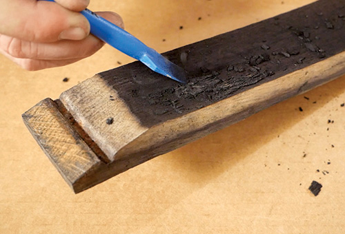 Scraping charred wood off a barrel stave